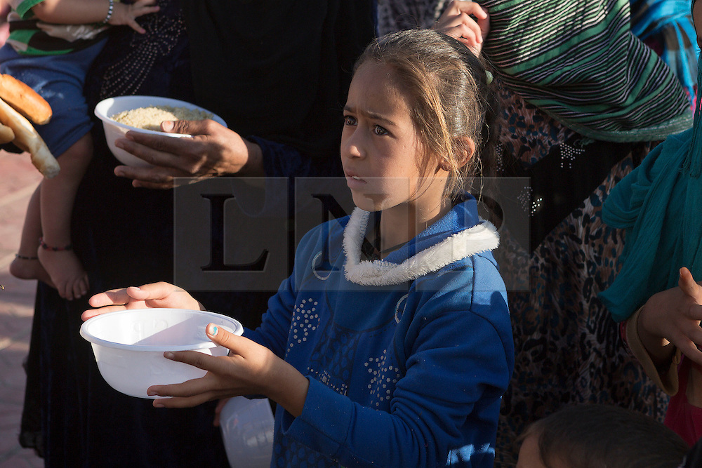 Licensed to London News Pictures. 22/10/2016. A young Iraqi girl, one of hundreds of newly arrived refugees coming from areas where the Mosul Offensive is taking place, waits to be given food by an aid worker in a school at the Dibaga refugee camp near Makhmur, Iraq. Upon arriving at the camp women and children stay in the school for around 10 - 15 days whilst completing the registration process.<br /> <br /> The crowded Dibaga camp, housing around 28,000 Sunni Arab refugees, is the main gathering point for new IDPs now fleeing areas where ISIS have been pushed out or are in conflict with the Iraqi Army. Photo credit: Matt Cetti-Roberts/LNP