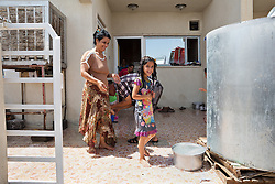 © Licensed to London News Pictures. Hamdaniyah, Iraq. 26/07/2014. Sahira Samir Kamal (L), an Iraqi Christian refugee from Mosul, washes her daughter Dilar (9) after being resupplied with fresh drinking water by Kurdish Zeravani soldiers at the partially built home they share with 15 other family members in Hamdaniyah, Iraq. Sahira and her family left Mosul on Friday the 18th of July when Islamic State fighters issued an ultimatum to the city's Christian community. When the family left they were forced to pay a tax for their car, their son (19) was threatened at knifepoint to ensure they handed over all of their possessions including family photographs.<br /> <br /> <br /> <br /> Having taken over Mosul Iraq's second largest city in June 2014, fighter of the Islamic State (formerly known as ISIS) have systematically expelled the cities Christian population. Despite having been present in the city for more than 1600 years, Christians in the city were given just days to either convert to Islam, pay a tax for being Christian or leave; many of those that left were also robbed at gunpoint as they passed through Islamic State checkpoints.. Photo credit : Matt Cetti-Roberts/LNP