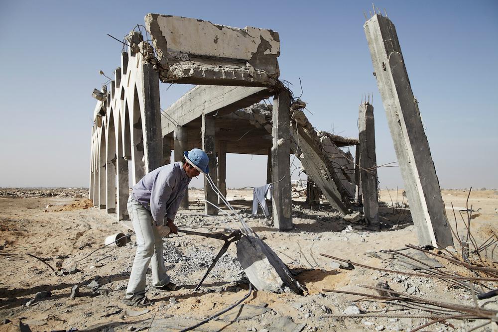 A man cuts a length of rebar from a destroyed pillar at Yasser Arafat International Airport.