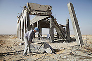 A man cuts a length of rebar from a destroyed pillar at Yasser Arafat International Airport.