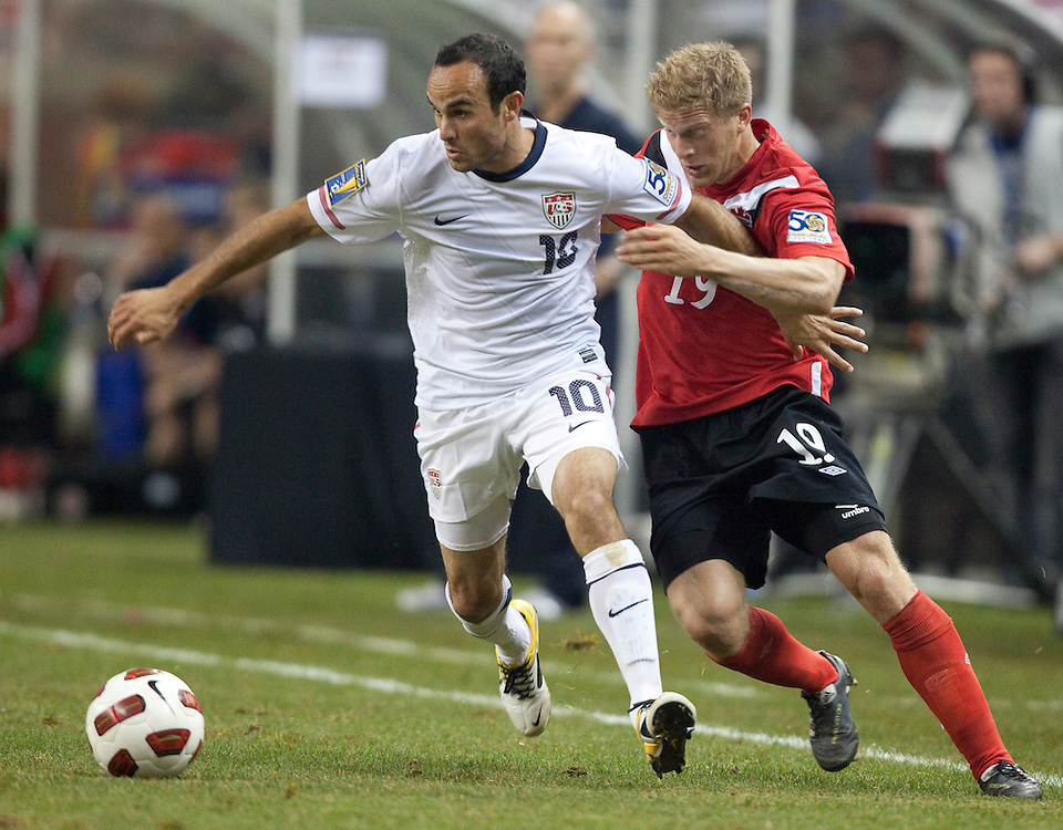 GR8007 -20110607- Detroit, Michigan,USA<br /> Landon Donovan of the United States strips the ball from Canada's Marcel Dejong during their CONCACAF match at Ford Field in Detroit Michigan, June 7, 2011.<br /> AFP PHOTO/Geoff Robins