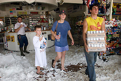 25 Sept 2005, Carlyss, Louisiana.  Hurricane Rita aftermath. <br /> Local cajun man Josh Herman (rt) helps locals and neighbours load supplies at Bayou Landing, his father's convenience store, despite the collapsed ceiling to keep people in basic food and supplies. <br /> Photo; ©Charlie Varley/varleypix.com