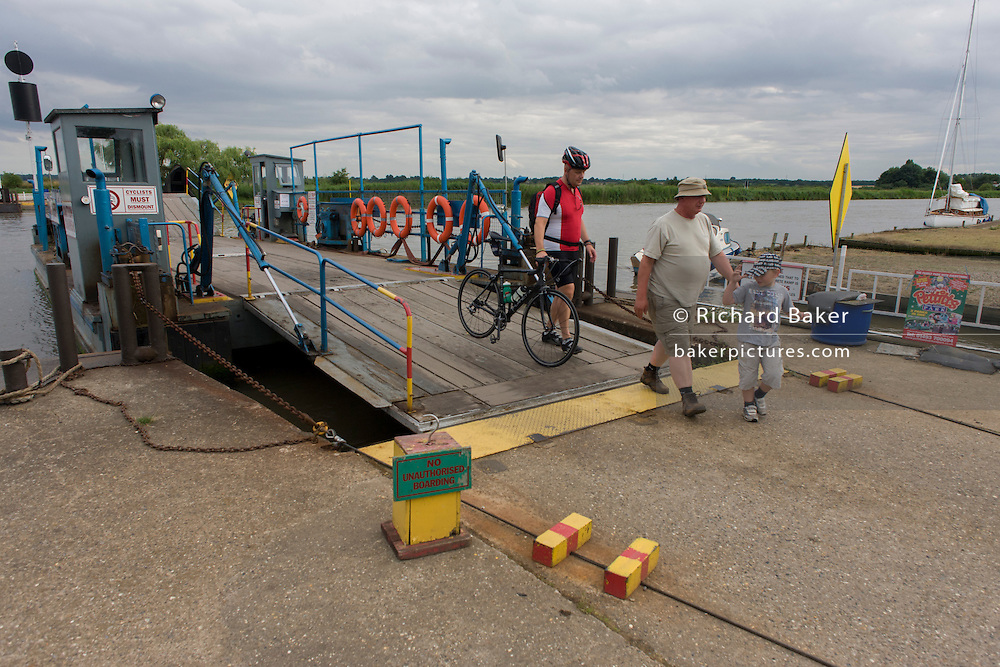Foot passengers disembarking the small chain ferry crossing the River Yare in Reedham on the Norfolk Broads.