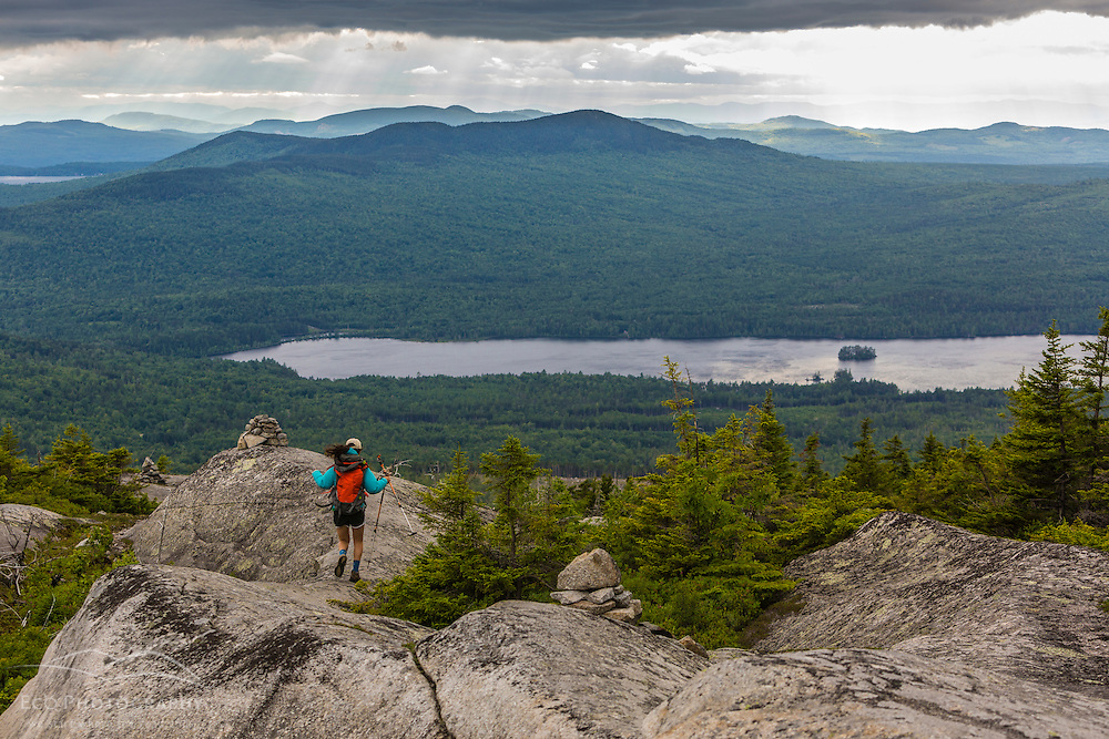 A teenage girl takes in the view from Moxie Bald Mountain. Moxie Pond is in the distance. Appalachian Trail. Bald Mountain Township, Maine.