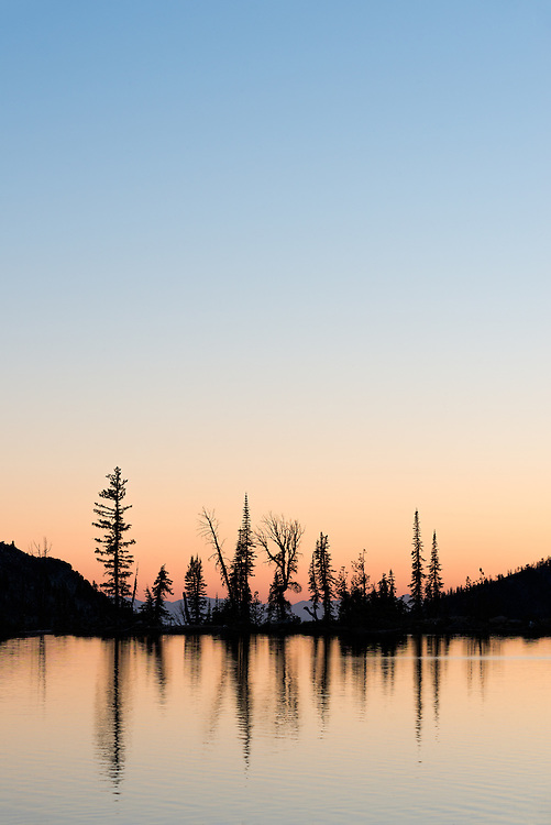 Trees reflected in a mountain lake at sunset, Wallowa Mountains, Oregon