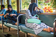 27 OCTOBER 2012 - SUNGAI KOLOK, NARATHIWAT, THAILAND:     Passengers rest in a third class compartment on the train going to Sungai Kolok, Thailand.  Sungai Kolok has been a center of extremist violence. Several car bombs have been detonated in the city, which is on the Malaysian border and very popular with Malaysian tourists. More than 5,000 people have been killed and over 9,000 hurt in more than 11,000 incidents, or about 3.5 a day, in Thailand's three southernmost provinces and four districts of Songkhla since the insurgent violence erupted in January 2004, according to Deep South Watch, an independent research organization that monitors violence in Thailand's deep south region that borders Malaysia.   PHOTO BY JACK KURTZ