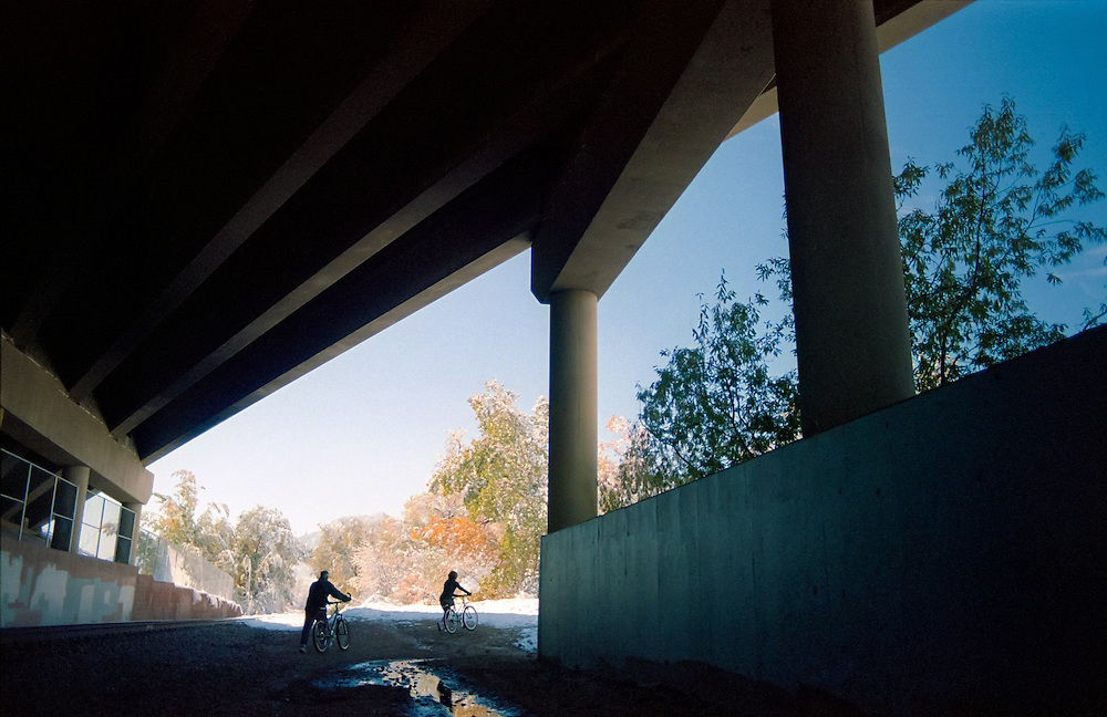 Bicycle riders walk their bikes under a highway overpass (Foothills Parkway) in Boulder, Colorado.