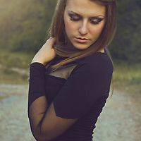 Elegant Young Woman wearing black dress looking down