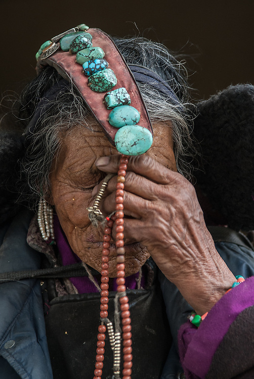 "An elderly Ladakhi woman wearing a ""perak,"" a headdress adorned with turquoise stones, and holding Buddhist prayer beads to her forehead."