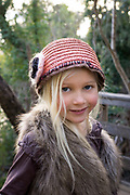 Cute blond girl in hat and faux fir vest in rural chic forest fashion clothing in a forest setting.