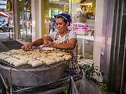 """04 OCTOBER 2012 - BANGKOK, THAILAND: A grilled banana vendor works on Sukhumvit Road near Soi 24 in Bangkok, Thailand. Thailand in general, and Bangkok in particular, has a vibrant tradition of street food and """"eating on the run."""" In recent years, Bangkok's street food has become something of an international landmark and is being written about in glossy travel magazines and in the pages of the New York Times.       PHOTO BY JACK KURTZ"""