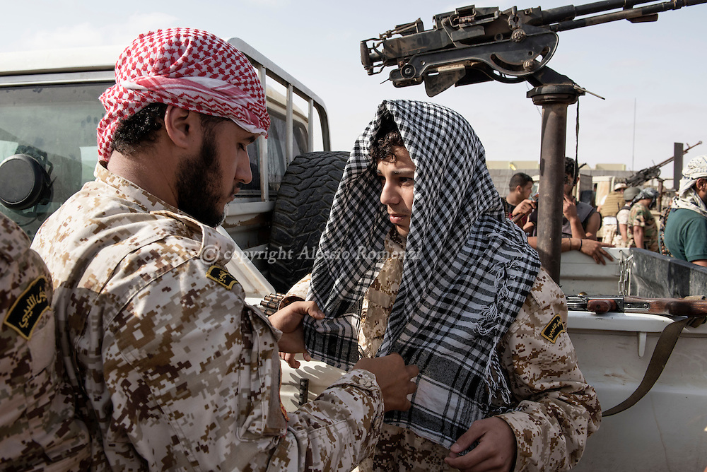 Libya: a fighter affiliated with Libya's Government of National Accord's (GNA) helps a comrade to dress the kufia as they wait to receive the order to assault  ISIS positions in 700 neighbourhood in Sirte. Alessio Romenzi