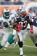MIAMI - DECEMBER 10:  Running back Kevin Faulk #33 of the New England Patriots runs the ball while avoiding a tackle by Vonnie Holliday #91 of the Miami Dolphins at Dolphin Stadium on December 10, 2006 in Miami, Florida. The Dolphins defeated the Patriots 21-0. ©Paul Anthony Spinelli *** Local Caption *** Kevin Faulk;Vonnie Holliday