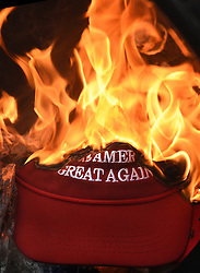 January 20, 2017 - Washington, DC, U.S - A hat with a Trump campaign slogan burns as protesters and police clash during President Donald Trump's inauguration in Washington, D.C., on Jan. 20, 2017. (Credit Image: © Carol Guzy via ZUMA Wire)