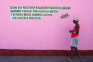 A woman walks pass a propaganda writing quoting Fidel Castro in a street of Santa Clara. Cuba, 2015.
