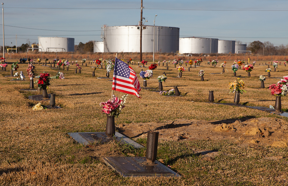 """Southern Memorial Garden cemetery in Scotlandville, Louisiana across from Exxon Mobile oil tanks.This site is located in the stretch between Baton Rouge and New Orleans along the Mississippi River has a large concentration of chemical and oil companies and was formerly referred to as the """"petrochemical corridor"""" but now is know as """"cancer alley"""" after numerous cases of cancer occurring in the small rural communities on both sides of the river were reported. The record high levels of the Mississippi River in the spring of 2011 brought on by what some scientists clasify as climate change,  threaten the environment with the potential flooding of industrial complexes and nuclear facilities along the river."""