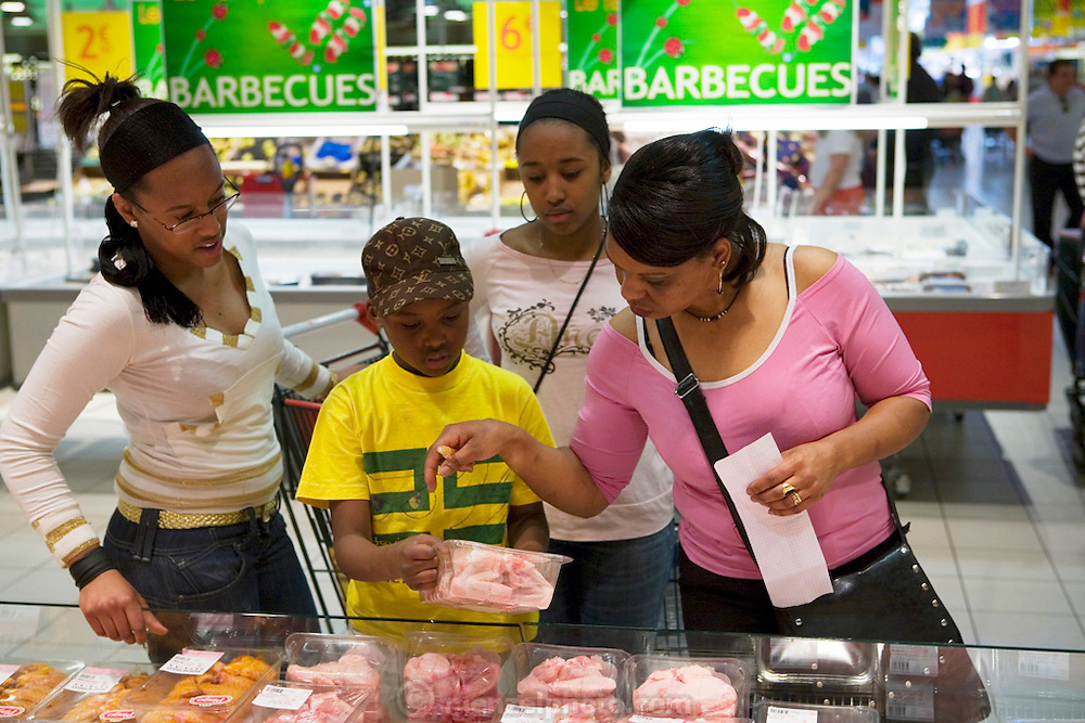 Maria Natercia Lopes-Furtado, of Rodange, Luxembourg, and three of their four children: Darlene, Melody, Teddy, shopping for one week's worth of food at an Auchan super market across the border in France near their home in the Grand Duchy of Luxembourg. The Lopes-Furtado family is from Cabo Verde living in Luxembourg. The image is part of a collection of images and documentation for Hungry Planet 2, a continuation of work done after publication of the book project Hungry Planet: What the World Eats.