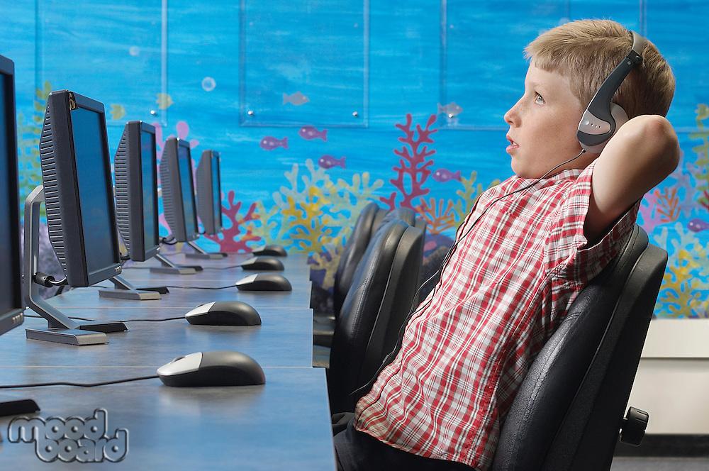 School boy wearing headphones, relaxing in computer room