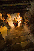 Looking down a stairway as a woman exits the Jain Temple in Jaisalmer Fort, Jaisalmer, India.