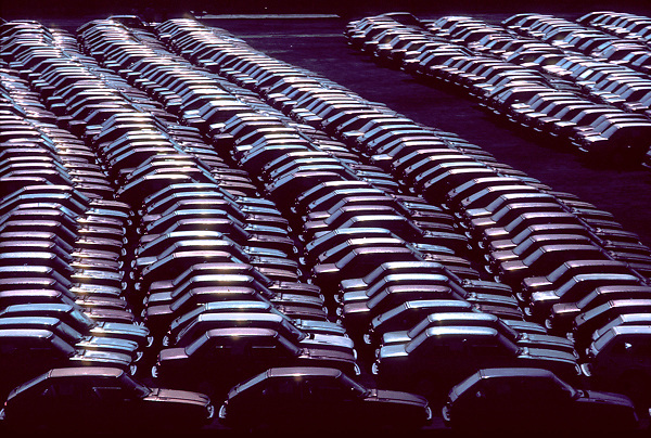 Stock photo of a large amount of cars parked at a manufacturer's storage facility