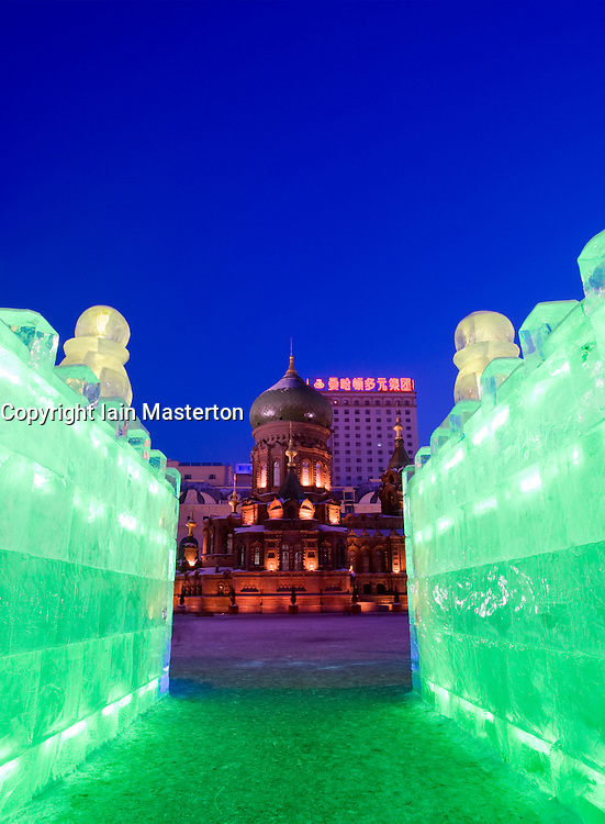 Saint Sophia church at night viewed from illuminated ice sculpture during annual ice lantern festival in Harbin China