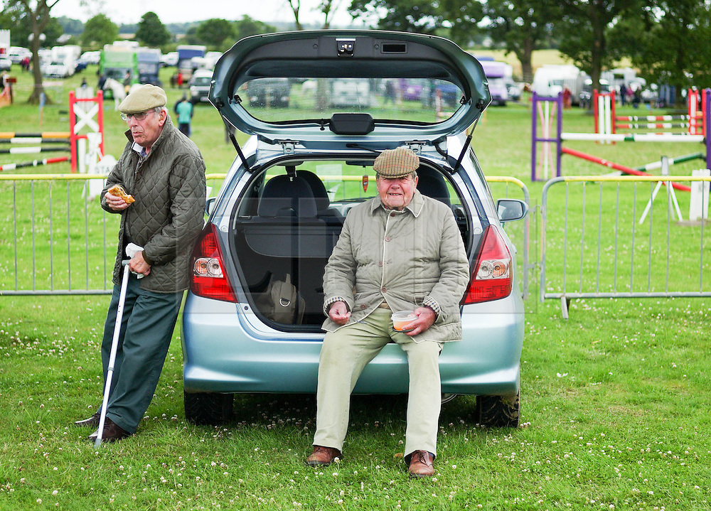 &copy; Licensed to London News Pictures.29/07/15<br /> Borrowby, UK. <br /> <br /> Two men have their lunch at the back of their car at the Borrowby Country Show and Gymkhana in North Yorkshire.<br /> <br /> Photo credit : Ian Forsyth/LNP