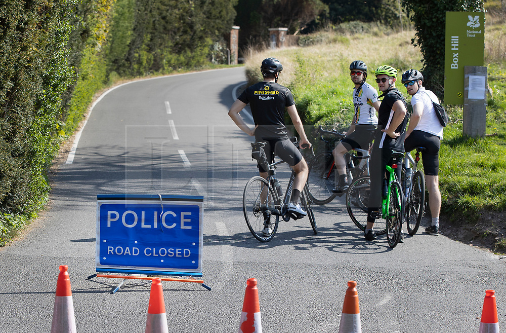 © Licensed to London News Pictures. 10/04/2020. Dorking, UK. Cyclists contemplate going up a closed Zig Zag road at Surrey beauty spot Box Hill near Dorking. Police have closed Box Hill over the Easter Weekend to stop the spread of the coronavirus . The government has warned that people must continue to follow the public health guidance over the Easter weekend. Photo credit: Peter Macdiarmid/LNP