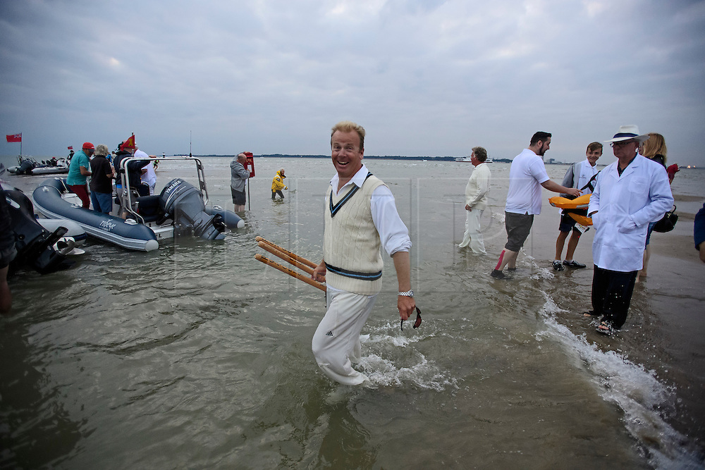 © Licensed to London News Pictures. 18/09/2016. Portsmouth, UK.  The wickets being carried out off the sea after the match. . Teams take part in the  Bramble Bank Cricket Match in the middle of The Solent strait on September 18, 2016. The annual cricket match between the Royal Southern Yacht Club and The Island Sailing Club, takes place on a sandbank which appears for 30 minutes at lowest tide. The game lasts until the tide returns. Photo credit: Ben Cawthra/LNP