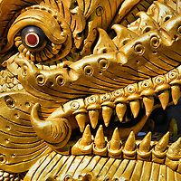 Nāga Extreme Close Up at Wat Chiang Man in Chiang Mai, Thailand <br /> Guarding the newest viharn at Wat Chiang Man is this golden nāga with a row of extremely sharp teeth, horns and a glowing red eye. The long, curving and scaled body of this mythological dragon winds up the staircase.