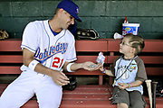 Doubledays third baseman Randy Schwartz and young fan Zachary Saurini, 7, of Auburn, share a bag of sunflower seeds before the team's season-opening game on June 18.<br /> <br /> Sam Tenney / The Citizen