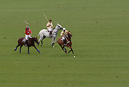 Town of Wallkill, NY -Three players race after the ball during a polo match at the Blue Sky Polo Club on Aug. 19, 2007l