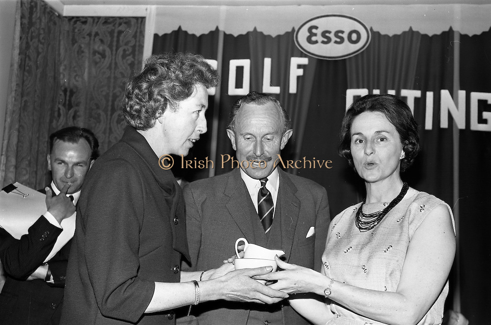 14/05/1965<br /> 05/14/1965<br /> 14 May 1965<br /> Esso Golf Outing at Woodbrook Golf Club, Bray, Co. Wicklow. Mrs J.H. Donovan, (right) wife of the Managing Director of Esso, presenting the Ladies prize to Miss Monica Mullins, Secretary to Managing Director. In centre is Mr R.A. Drew, Dublin Manager, Esso and Chairman Golf Committee.