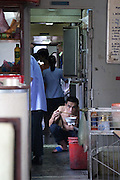 A man squatting eating noodles in the staff canteen of the Vietnam Railways Saigon to Hanoi train, Vietnam