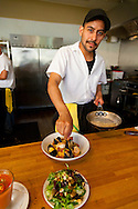 One of the line chefs putting the finishing touches on the house special paella at Andaluz Restaurant in Salem, Oregon