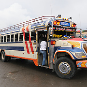 Riding chicken buses behind the Mercado Municipal (town market) in Antigua, Guatemala. From this extensive central bus interchange the routes radiate out across Guatemala. Often brightly painted, the chicken buses are retrofitted American school buses and provide a cheap mode of transport throughout the country.