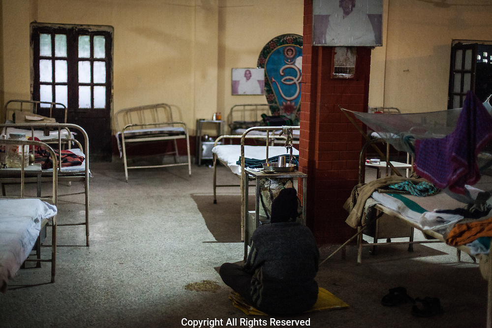 A lone male patient sits on the floor.