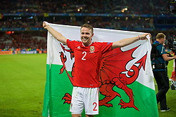 LILLE, FRANCE - Friday, July 1, 2016: Wales' Chris Gunter celebrates with a red dragon Welsh flag after a 3-1 victory over Belgium and reaching the Semi-Final during the UEFA Euro 2016 Championship Quarter-Final match at the Stade Pierre Mauroy. (Pic by David Rawcliffe/Propaganda)