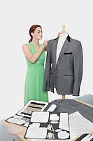 Female designer adjusting coat on tailor's dummy over gray background
