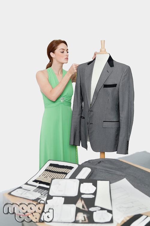 Female designer adjusting coat on tailor's dummy over gray background