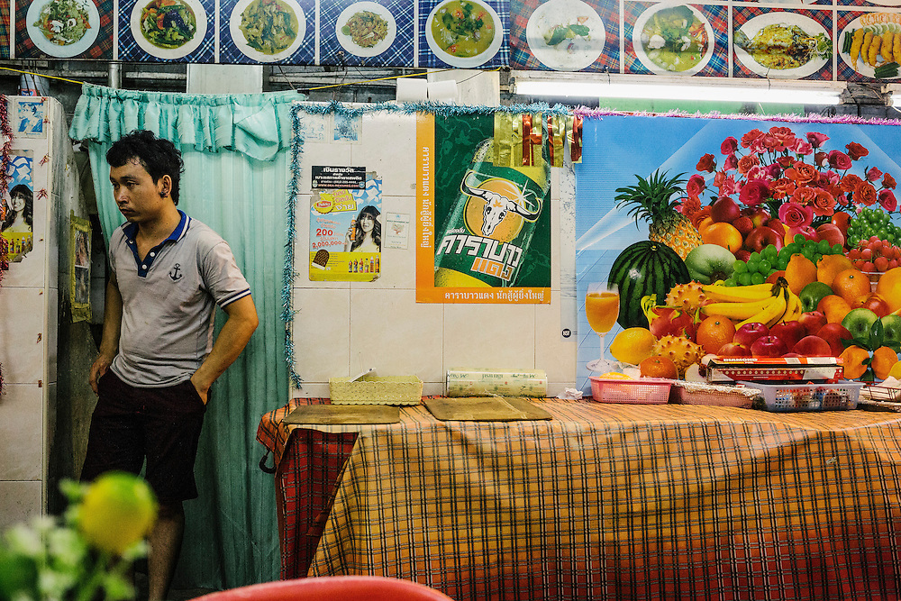 A Thai man waits for customers at his local restaurant that occupies a small alleyway adjoining Bangla Street.