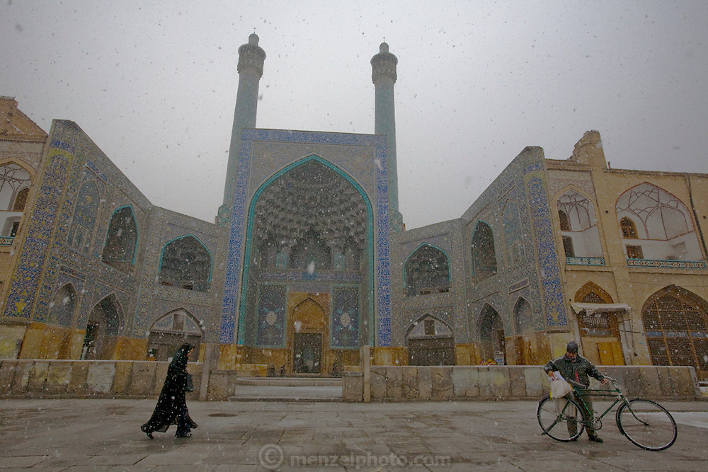 The courtyard of the magnificently tiled Masjed-e Imam (Royal Mosque) and its reflection at night in Imam Square, Isfahan, Iran. (Also referred to as Emam Square). The mosque was built by the Safavid ruler, Shah Abbas 1, as part of the renovation of the central square of Isfahan. The architect was Ostad Abu'l-Qasim.  (Imam Square is also called Naghsh-i Jahan Square).