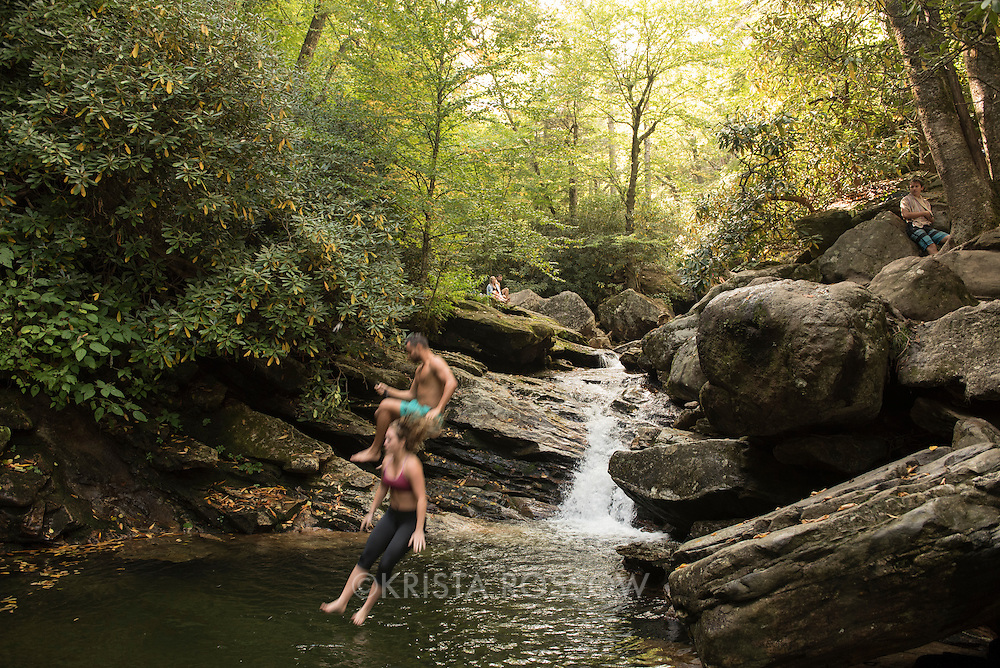 A couple jump from a rock into a swimming hole. Skinny Dip Falls is a popular waterfall and swimming hole along the Blue Ridge Parkway in the Pisgah National Forest southwest of Asheville, North Carolina. The half-mile long trail is accessed from the parking lot at the Looking Glass Rock Overlook at milepost 417.