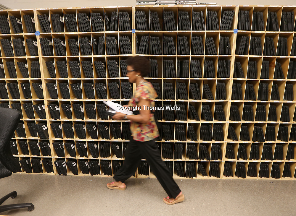 Joan Kelsie makes her way past a wall stacked with computers waiting to be picked up by students at Tupelo High School Monday morning.