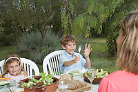 Mother and two children (5-6) at table in garden