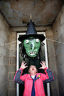 A woman screams at a massive witches head made from paper and cardboard