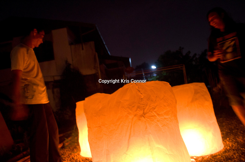 Two men light khom fais at a hostel in the old city during Loi Kratong in Chiang Mai, Thailand. Photo by Kris Connor