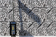 The shadow of an outdoor pay phone is cast against an exterior wall.  The wall is covered in the same black and white poster repeated over and over again to create a  pattern on the wall.   an exterior wall.