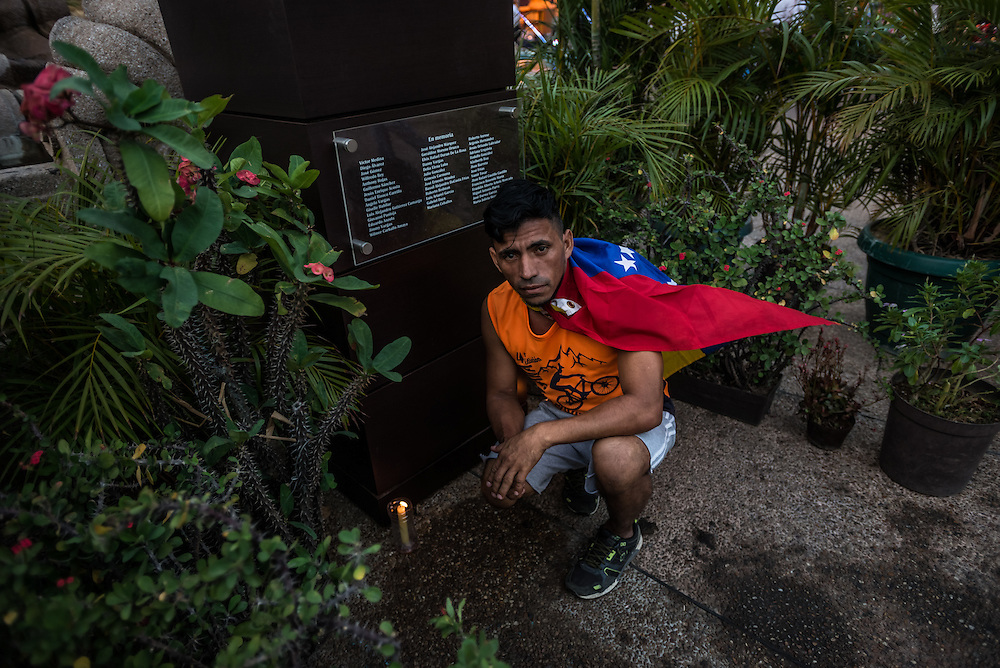 CARACAS, VENEZUELA - MAY 7, 2015:  Felix, an opposition protest leader lights a candle underneath a memorial in Plaza Francia in Eastern Caracas to all the opposition protesters that were killed last year during protests against the government for growing inflation, shortages, and insecurity.  The police have detained several opposition protesters in this plaza, and recently the bodies of two protest leaders surfaced at the morgue, shortly after being detained by the police.  PHOTO: Meridith Kohut for Buzzfeed News