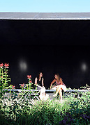 © licensed to London News Pictures. LONDON, UK.  27/06/11. Two women enjoy a seat next to the garden designed by Dutch designer Piet Oudolf. Press view of the Serpentine Gallery Pavilion 2011, in Hyde Park today (27 June2011). Mandatory Credit Stephen Simpson/LNP