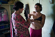 Sheza Shahnawaz, a 42 year old Hijra is the Guru (leader) assists Sonya, a 32 year old Hijra to dress for the evenings work on the streets of Karachi...The word Hijra is an Urdu word meaning eunuch or hermaphrodite. However, most Hijras in Pakistan are gay men who leave home to join the Hijra community as young boys where there is more acceptance. Most identify themselves as more feminine then masculine and dress and act accordingly...Although tolerated in a country where homosexuality is against the law, Hijras are largely ostracised from society. They are often denied work opportunities, rejected by most families, lack formal education and live in poorer areas of the city...They share similarities with the more famous Hijra communities in the Indian subcontinent and Bangladesh. In a continent where great emphasis is placed on one's ability to have children, those who are unfortunate not to be able to conceive children are not considered a true man or woman. Life for many Hijras in Pakistan consists of begging for alms (Zakat) in the more prosperous areas of the city as well as slums in addition to receiving alms when bestowing blessings on male babies and at weddings....Most Hijras dress as women, and engage in activities such as dancing and entertaining in public - activities that would be considered inappropriate for women of the subcontinent. Some members of the community engage in prostitution. .